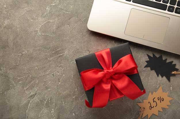 Zwarte vrijdag. online shopping concept met geschenkdoos op grijs.
