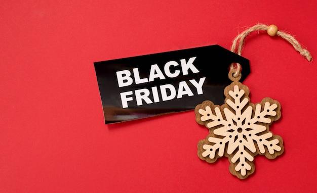 Zwarte vrijdag op rode achtergrond met houten sneeuwvlok