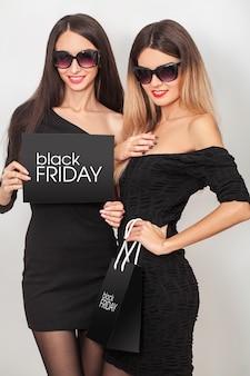 Zwarte vrijdag. uitverkoop. twee jonge glimlachende vrouwen die het winkelen zak in zwarte vrijdagvakantie tonen