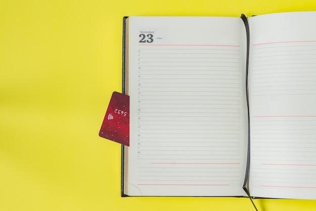 Zwarte vrijdag verkoop concept. boodschappenlijstje in notitieblok en bankkaart als bladwijzer
