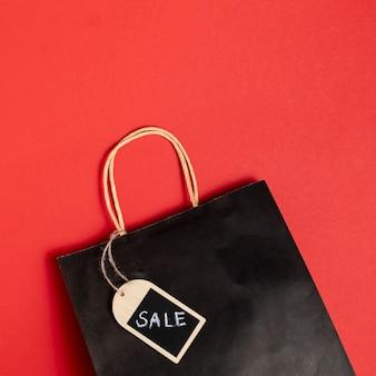 Zwarte vrijdag verkoop papieren zak op rode achtergrond