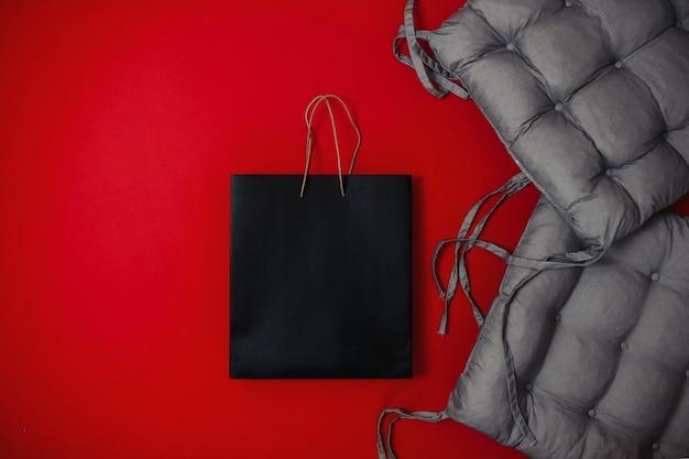 Zwarte vrijdag verkoop plat lag, banner voor thuis goederen winkel, zacht grijs kussen en zwarte tas op het rode oppervlak,