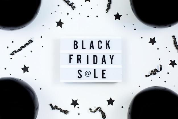 Zwarte vrijdag verkoop tekst op witte lightbox en zwarte ballonnen en confetti