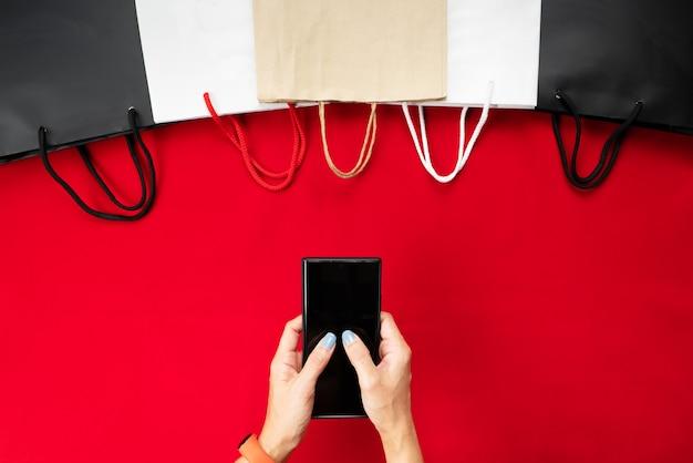 Zwarte vrijdag verkoop, vrouw hand online winkelen op smartphone met boodschappentas op rode achtergrond