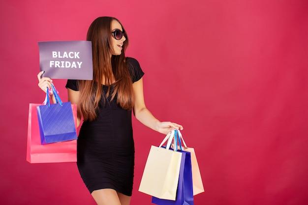 Zwarte vrijdag. vrouw met de inscriptie black friday en geschenkzakken