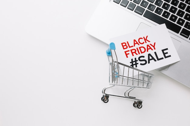 Zwarte vrijdag winkelwagentje en laptop met kopie ruimte