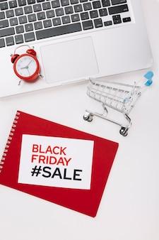 Zwarte vrijdaglaptop met het concept van de boodschappenwagentjeverkoop