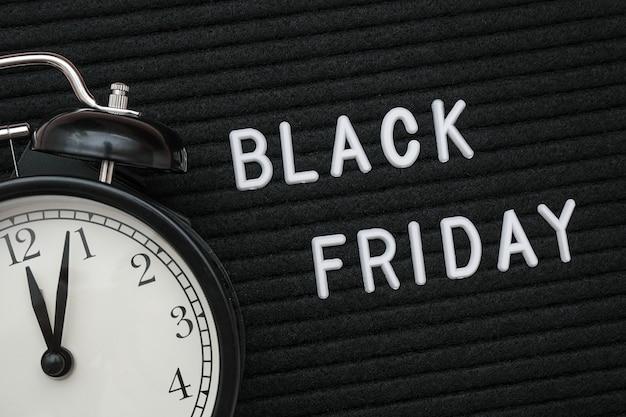 Zwarte vrijdagtekst op zwart brievenbord en wekker