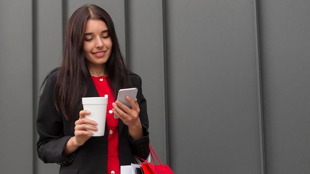 Zwarte vrijdagverkoopvrouw met koffie en mobiele telefoon