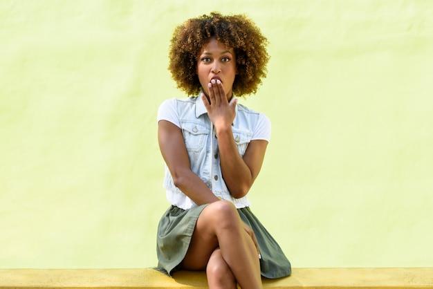 Zwarte vrouw, afrokapsel, zittend met een verrassingsgezicht