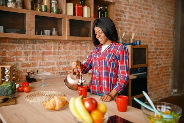 Zwarte vrouw bereidt koffie op het ontbijt in de keuken. afrikaanse vrouwelijke persoon die groentesalade thuis voorbereidt