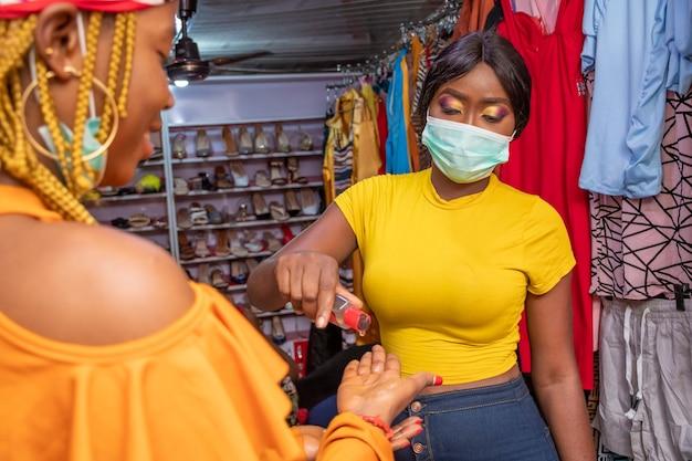 Zwarte vrouw die een boetiek heeft die handdesinfecterend middel voor een klant uitdeelt