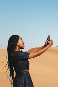 Zwarte vrouw die een foto maakt op een woestijn