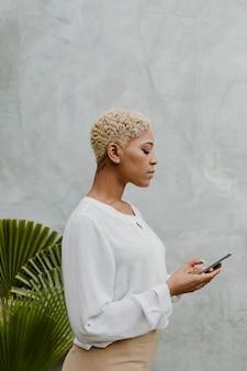 Zwarte vrouw die haar mobiele telefoon gebruikt