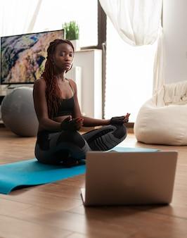 Zwarte vrouw die op yogamat zit en kalme harmonie beoefent, mediterend zen voor een gezonde levensstijl, ontspannen in lotushouding. luisterinstructeur instructie tijdens online training.