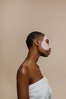 Zwarte vrouw doet een gezichtsmasker