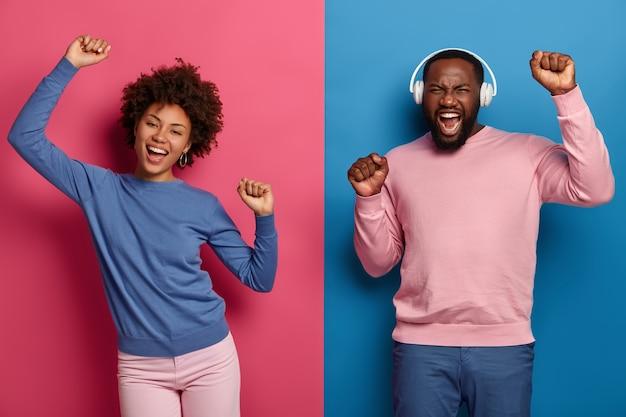 Zwarte vrouw en man voelen zich geamuseerd, dansen samen, houden de armen omhoog, hebben zorgeloze uitdrukkingen, geven niet om de mening van mensen