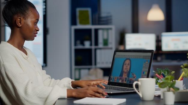 Zwarte vrouw foto retoucher werkt op laptop bij nieuw project