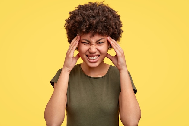 Zwarte vrouw fronst gezicht van ongenoegen, klemt haar tanden op elkaar, houdt de handen op de slapen