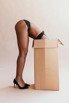 Zwarte vrouw in een beha die zich in een kartonnen doos buigt