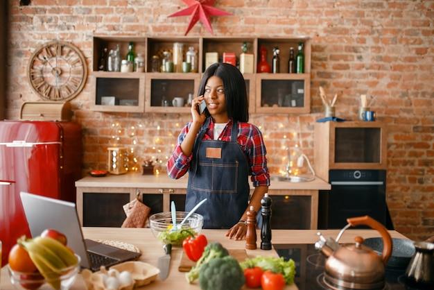Zwarte vrouw in schort praten via de mobiele telefoon op de keuken. afrikaanse vrouwelijke persoon die groentesalade thuis voorbereidt, etnisch meisje dat gezond ontbijt kookt