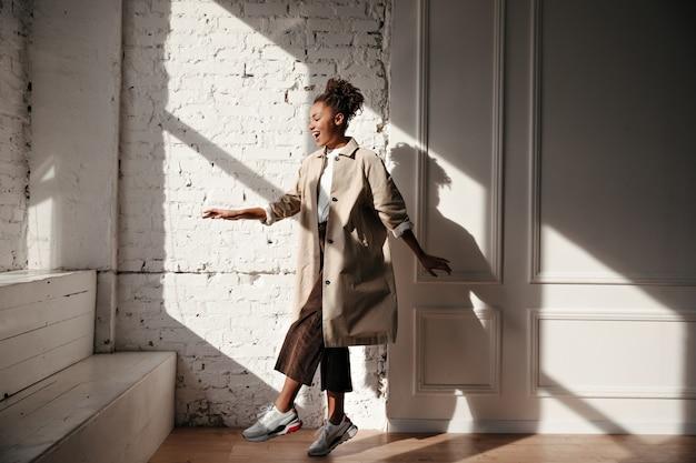 Zwarte vrouw in trenchcoat dansen onder zonlicht