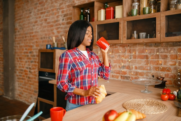 Zwarte vrouw koken gezond ontbijt op keuken