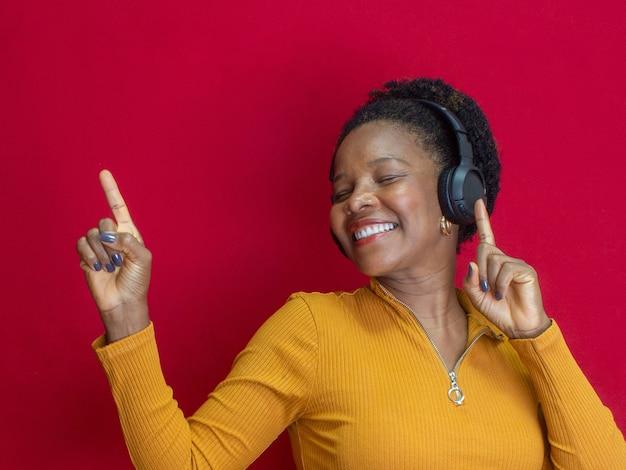Zwarte vrouw lacht en doet een gebaar en luistert naar een lied met een geel shirt op een rode achtergrond