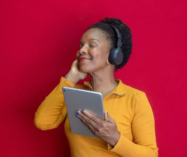 Zwarte vrouw lacht en houdt een tablet vast, doet een gebaar en luistert naar een liedje met een geel shirt op een rode achtergrond