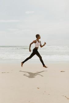 Zwarte vrouw loopt op het strand