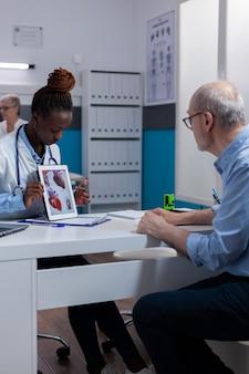 Zwarte vrouw met artsenberoep die organenillustratie tonen