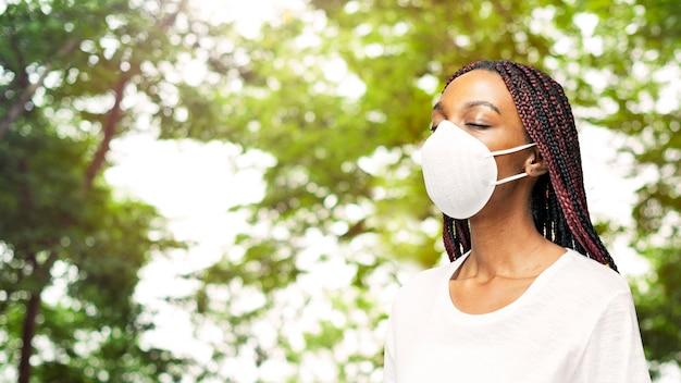 Zwarte vrouw met een luchtvervuilingsmasker in een park