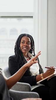 Zwarte vrouw met een notitieblok in een vergadering