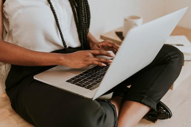 Zwarte vrouw met een notitieboekje op haar schoot op een houten vloer