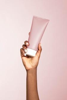 Zwarte vrouw met een tube schoonheidscrème