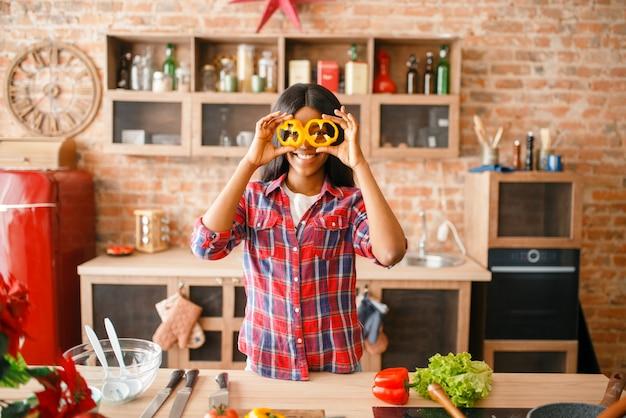 Zwarte vrouw met plezier op de keuken. afrikaanse vrouwelijke persoon die groentesalade thuis voorbereidt. gezonde levensstijl