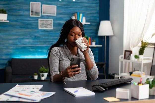 Zwarte vrouw met smartphone in handen en chat met mensen die communicatie-informatie doorbladeren