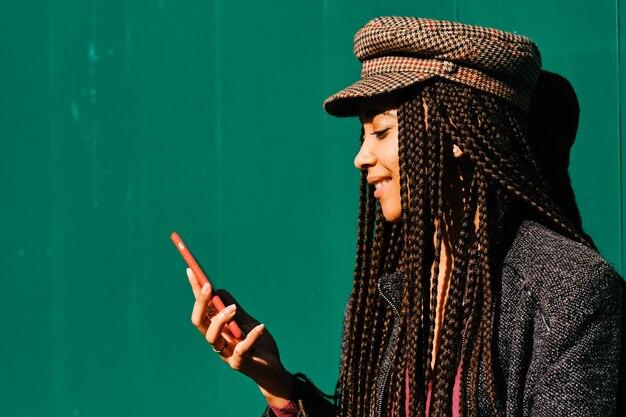 Zwarte vrouw met vlechten met behulp van een smartphone buitenshuis