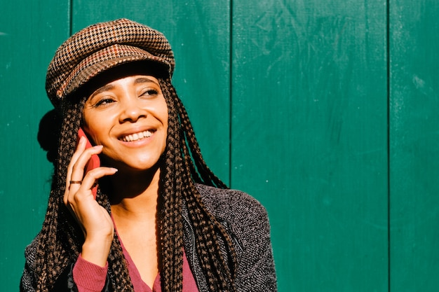 Zwarte vrouw met vlechten telefoongesprek met smartphone