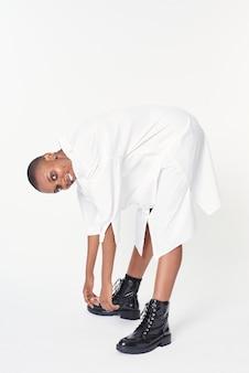 Zwarte vrouw met zwarte enkellaarzen in een witte jurk
