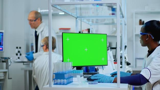 Zwarte vrouw onderzoeker kijken naar chroma key computer in modern uitgerust lab. multi-etnisch team van microbiologen die vaccinonderzoek doen en schrijven op apparaat met groen scherm, geïsoleerd, mockup-display.