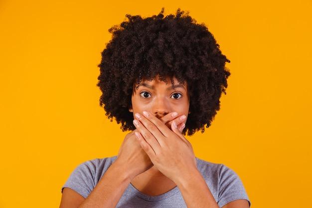 Zwarte vrouw op geel met hand in mond, concept van misbruik, feminicide, racisme en vooroordelen