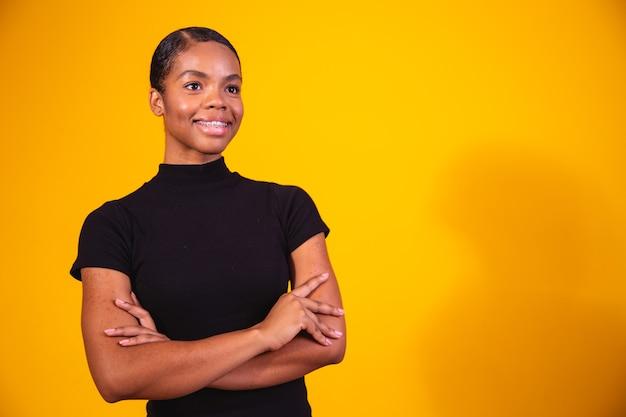 Zwarte vrouw op gele achtergrond met gekruiste armen. zakenvrouw op gele achtergrond