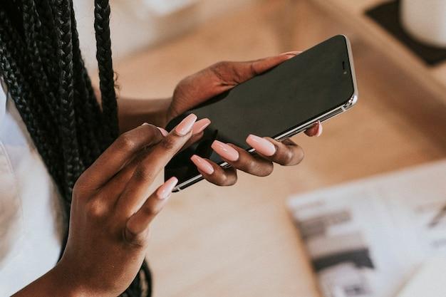 Zwarte vrouw sms't op haar mobiele telefoon