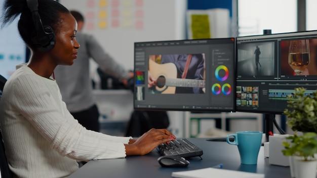 Zwarte vrouw video-editor die nieuwe projectfilmmontage bewerkt, zittend in een modern kantoor van een creatief bureau c...