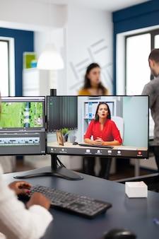 Zwarte vrouw videograaf in online webconferentie met projectmanager over het bewerken van videogesprekken met klanten, feedback krijgen op commerciële film met behulp van postproductiesoftware op pc in startkantoor