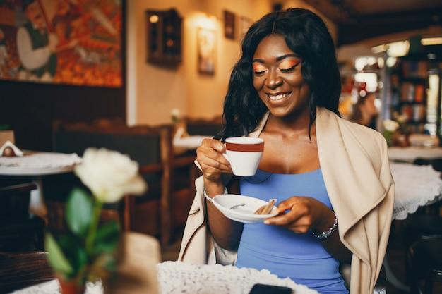Zwarte vrouw zitten in een café