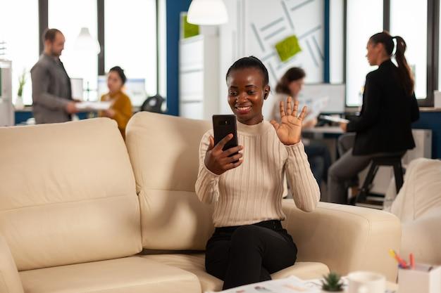Zwarte vrouw zwaait naar camera en legt financiële rapporten uit aan externe manager tijdens videogesprek met smartphone met koptelefoon zittend op de bank
