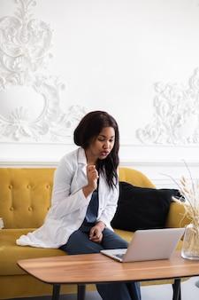 Zwarte vrouwelijke arts telegeneeskunde het gebruik van computer- en telecommunicatietechnologieën voor de uitwisseling van medische informatie
