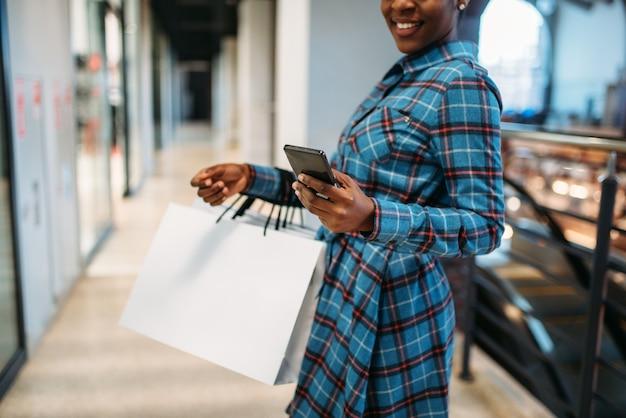 Zwarte vrouwelijke persoon met telefoon en boodschappentassen in winkelcentrum. shopaholic in kledingwinkel, levensstijl van consumentisme, mode